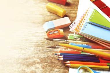 Bright school stationery on table
