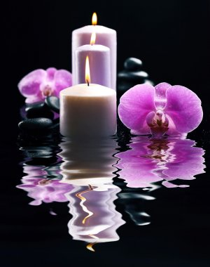 Composition of orchids, pebbles and candles