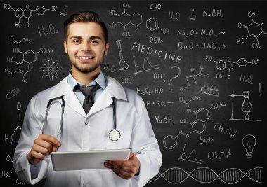 Doctor with tablet near blackboard