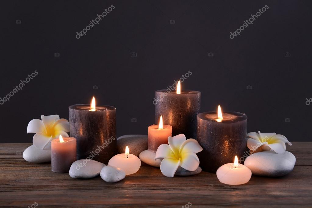 spa stones with burning candles and flowers stock photo