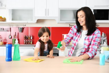 Daughter and mother cleaning kitchen table