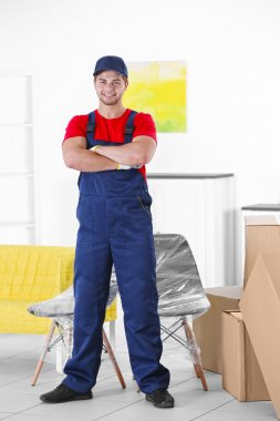 Male worker with boxes and furniture in new house