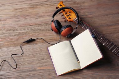 Headphones, guitar and notebook