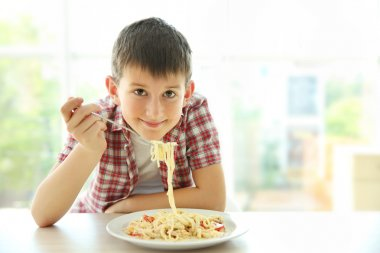 Cute boy eating spaghetti