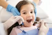 Zubař vyšetřující dívčí zuby