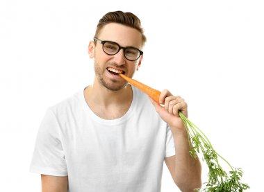 Handsome man eating carrot