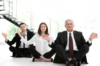 Business people relaxing in meditation pose