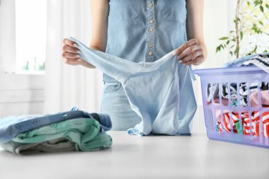 Woman folding clothes in laundry