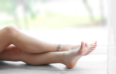 Female legs with tattoo