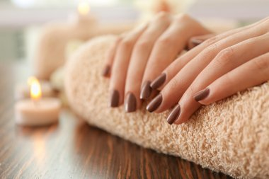 Female brown manicure on towel