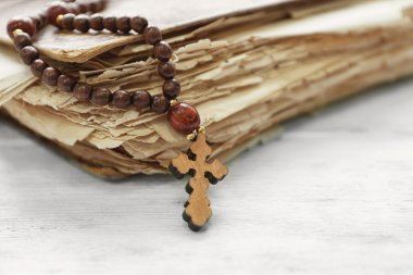 Wooden cross and old book, closeup