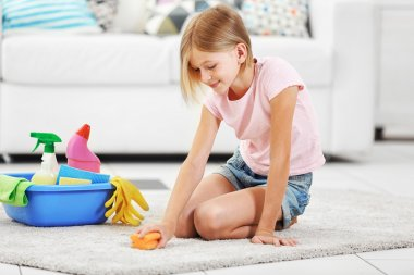 Little girl cleaning floor carpet
