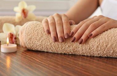 Female brown manicure on towel, closeup