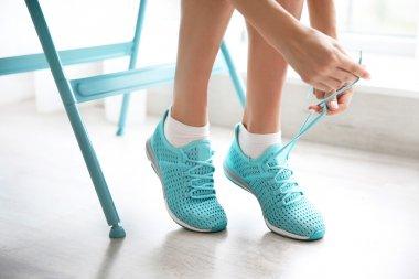 Woman tying her mint sneakers