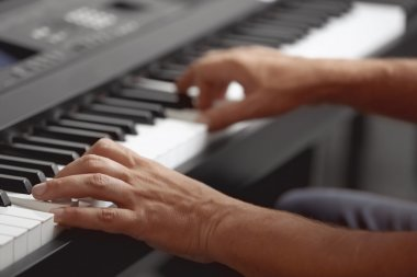 hands playing on synthesizer