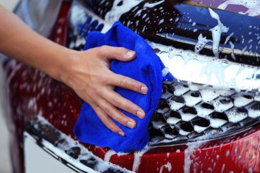 Serviceman washing a car