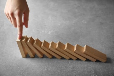 hand stopping domino effect