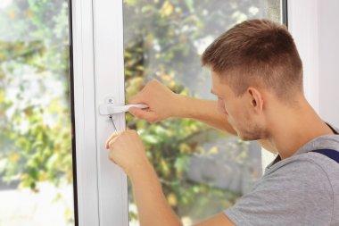 Construction worker repairing window handle