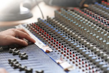 Hand on mixer in recording studio