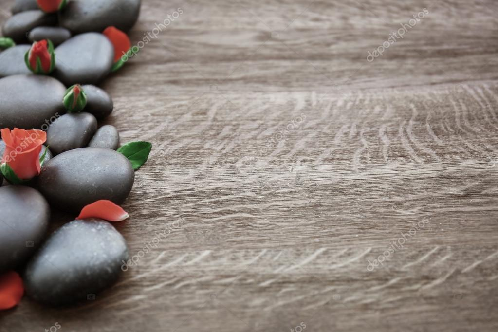 Spa stones with rose and petals on wooden background