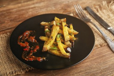 Fried eggplant on black plate on wooden background