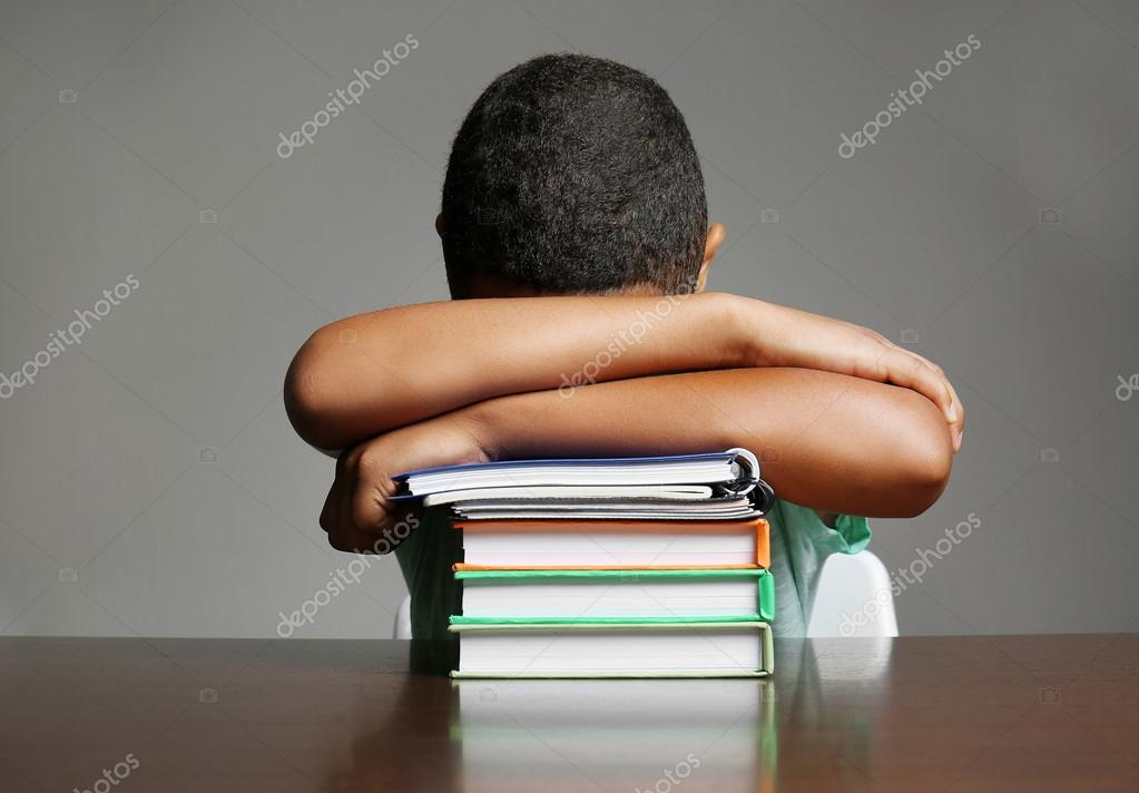 African American boy sleeping on books