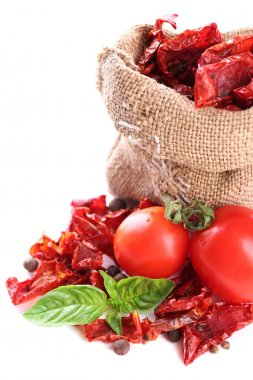 Sun dried tomatoes in sackcloth bag and basil leaves, isolated on white