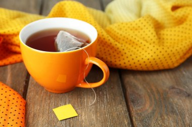 Cup of tea with tea bag on wooden table close-up