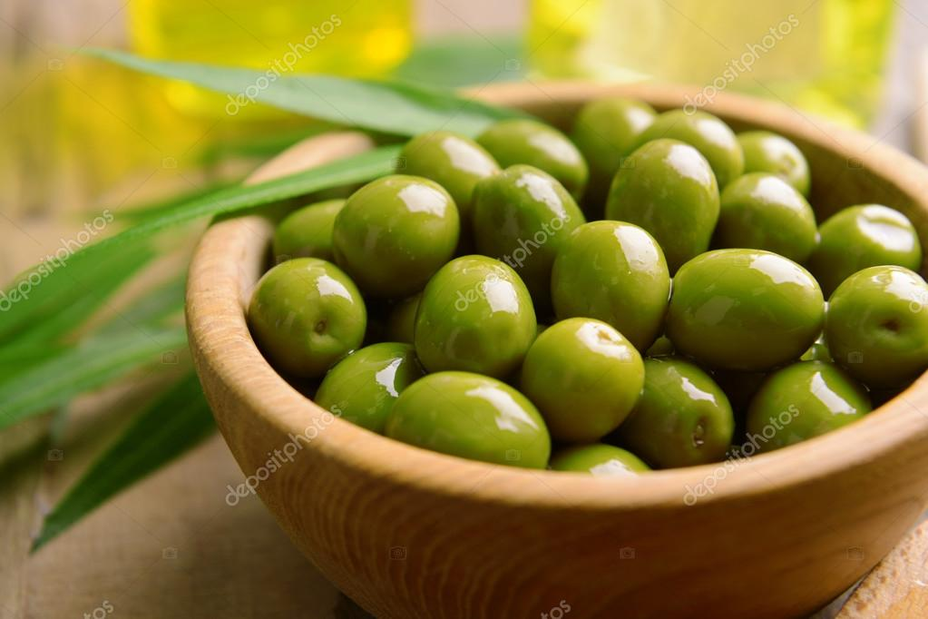 Green olives in bowl with leaves