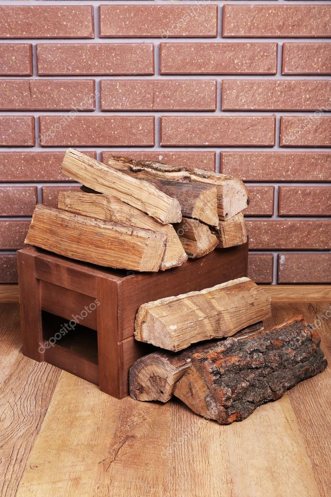 Wooden Box Of Firewood On Floor On Brick Background Stock Photo