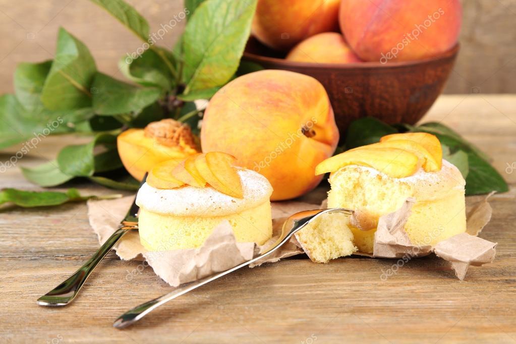 Leckere mini kuchen mit frischen pfirsich auf holztisch for Minikuche mit elektrogeraten