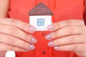 žena ruce drží malý dům zblízka