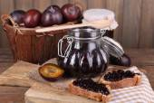 Photo Tasty plum jam in jars and plums on wooden table on wooden background