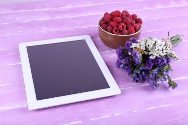 Tablet, flowers and bowl of raspberries