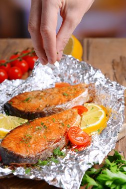 Tasty baked fish in foil on table close-up