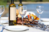Fotografie Picnic table with skewers and wine, close-up