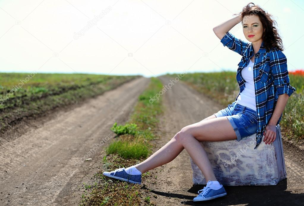 Beautiful young woman sitting sits on suitcase on countryside road