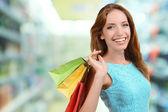 Fotografie Shopping-Konzept. Schöne junge Frau mit Einkaufstüten auf Geschäft Hintergrund