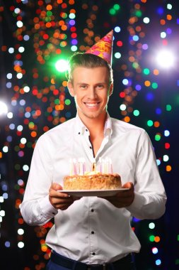 Young man with cake in club