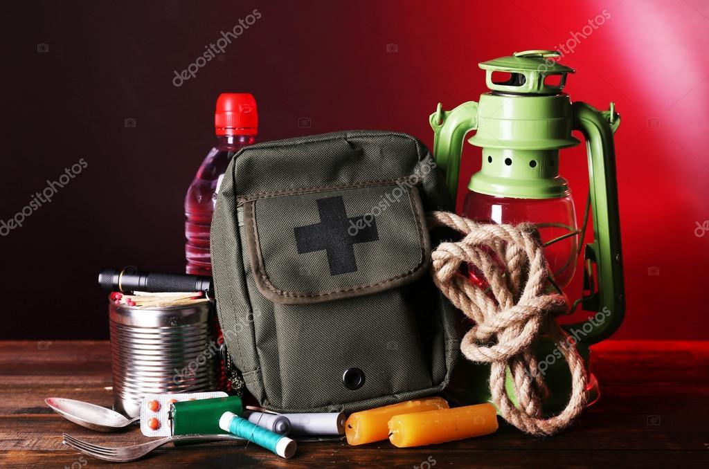 Emergency preparation equipment on wooden table, on dark background