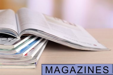 Magazines on wooden table, bright background