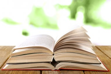 Three open books on wooden table on natural background