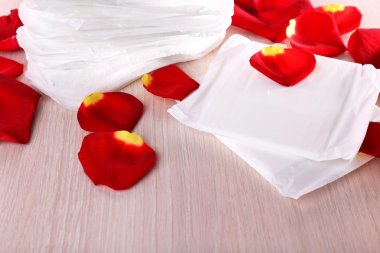 Sanitary pads and rose petals on table on wooden table on pink background