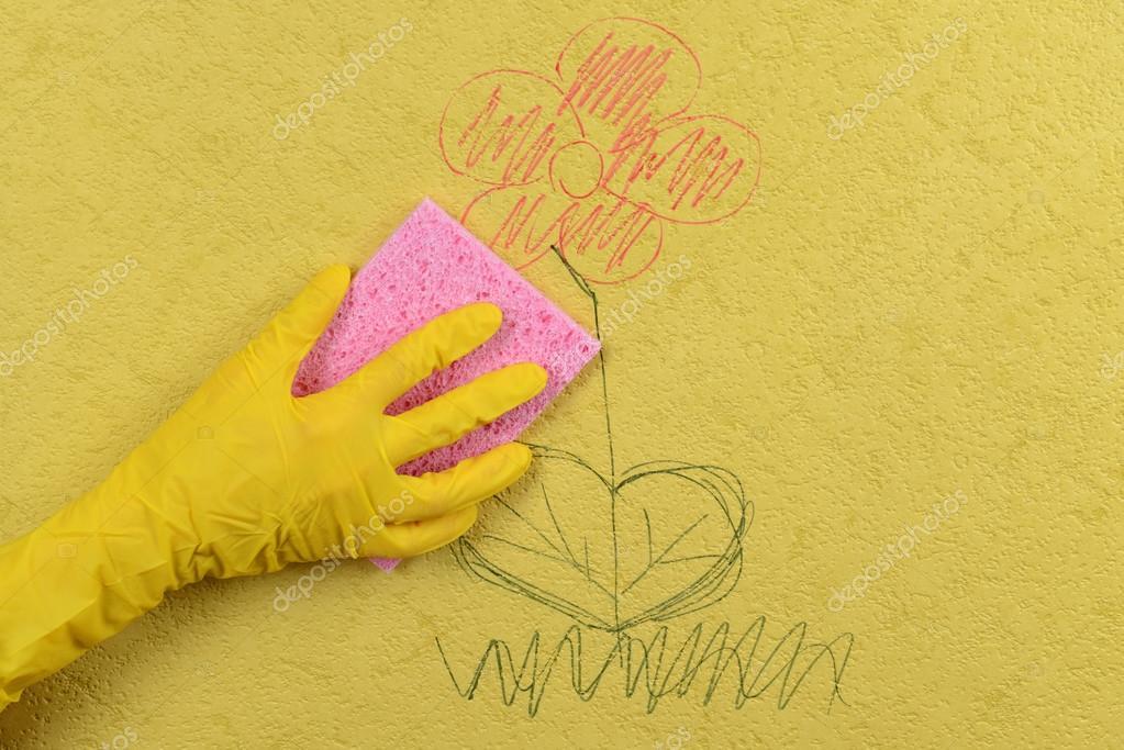 mano en guante limpiando a los niños dibujando en papel pintado ...