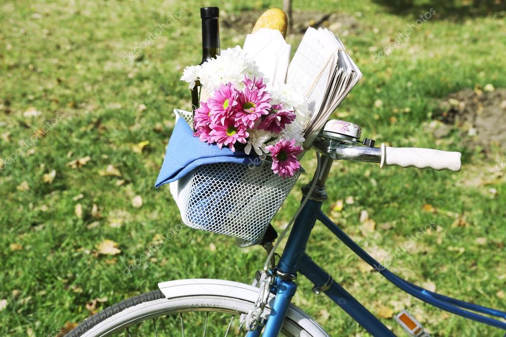 Bicycle with flowers, bread and bottle of wine in metal basket on grass background