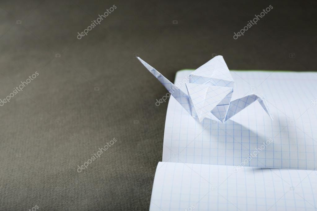 Origami Cranes On Notebook On Grey Background Stock Photo