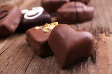 Various of sweet candy on wooden textured background with chocolate heart foreground