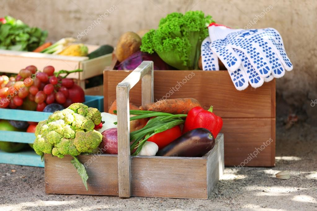 Fresh organic fruits and vegetables in wooden boxes outdoors