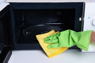 Cleaning microwave oven in kitchen close-up