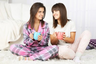 Beautiful girls twins in pajamas drinking tea at home